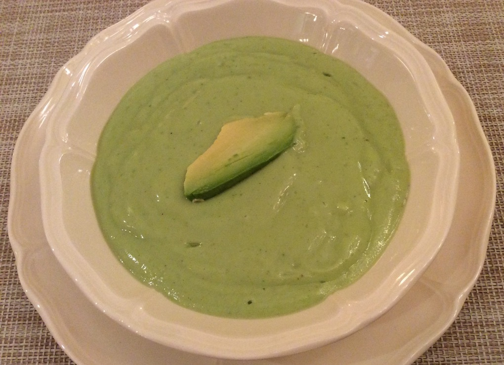 Bowl of green soup with avacado garnish