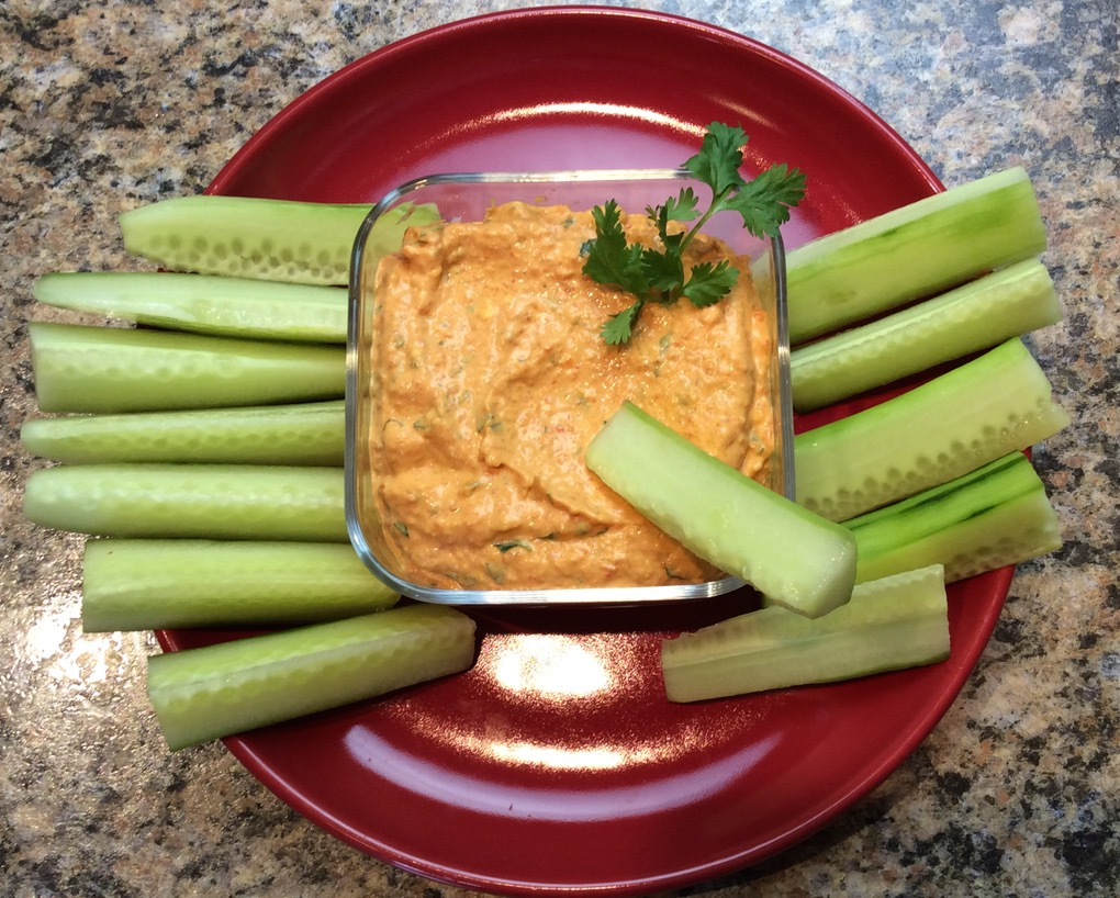 Serving dish wtih dip surrounded by cucumber sticks