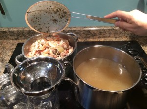 Lifting solids from the broth pot into a colander