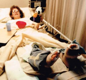 Sally in hospital bed with two feet bandaged and wrapped in ice.
