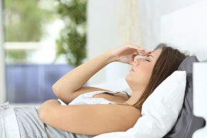 profile of a woman suffering head ache lying on the bed at home