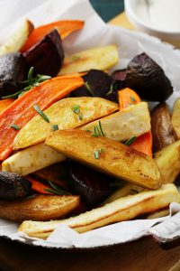 Bowl of roasted root vegetable wedges. Potato, beets, and carrots.