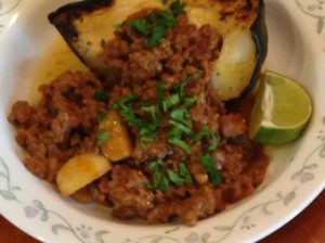 Dish of Chili served with acron squash and garnished with chopped cliantro and lime wedge