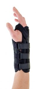 close up of person wearing supportive black brace on wrist secured with velcro straps
