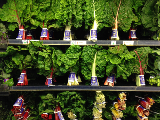 Three Grocery Produce shelves filled with bundles of fresh swiss chard standing upright