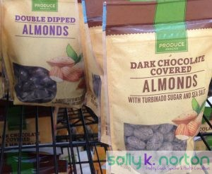 Bags of chocolate covered almonds on a supermarket produce shelf.