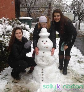 Three young women in black with their snow person construction