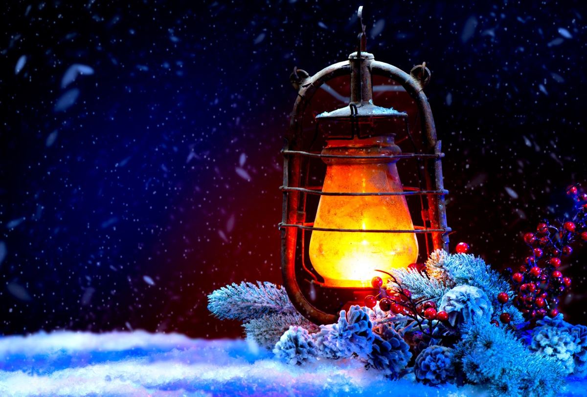 Still life night scene photo: Winter Lit Lantern standing on snow with frosted greens and pine cones
